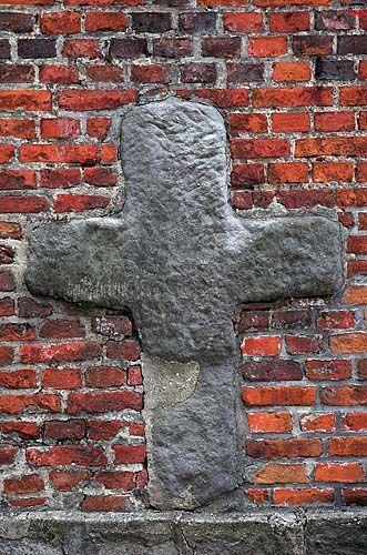 Konin, kamienny krzyż na murze kościoła parafialnego