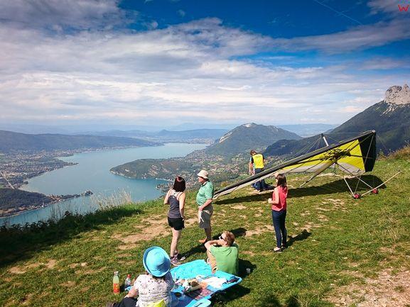 Montmin (Francja), 12.09.2015. Lotniarz w trakcie przygotowywania siÄ™ do lotu tandemowego na tle jeziora Jezioro Annecy