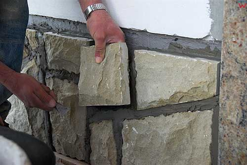 Robornik ukladajacy plyty kamienne na scianie.